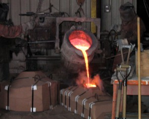 The figure shows molten silicon bronze being used in a sand casting procedure.